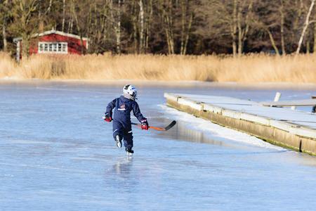 ni�o en patines: Listerby, Suecia - 17 de enero 2016: Un muchacho joven desconocida est� patinando con un palo de hockey sobre todo en la Marina en Blekinge costera. El muchacho se ve desde la parte posterior.