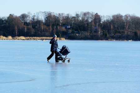 Listerby, Sweden - January 17, 2016: An unknown female is walking on the sea ice with a Brio stroller. She is waiving to the child. She is far out on the sea with the coastline behind her.