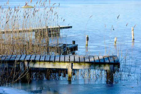 coldness: A small wooden pier is surrounded by ice and reed. The coldness has taken a grip over the landscape. Stock Photo