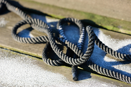 tie: Close up of a black rope on a frosty wooden pier one sunny winter day.
