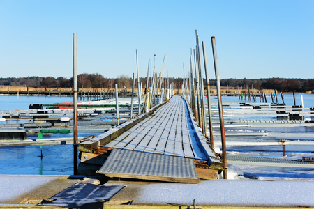 floating bridge: A tilting wooden floating bridge on a marina in winter. The ice has made the bridge lean to its side. No boats in mooring places. Sea is frozen solid in the cold weather. Listerby, Sweden. Stock Photo
