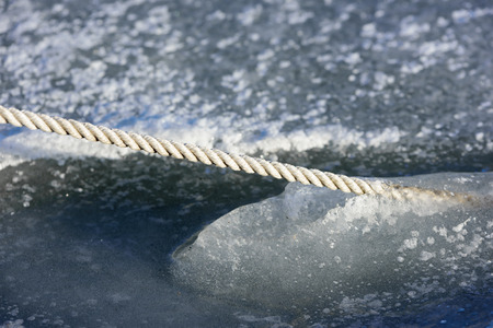 twined: Close up of white rope frozen in the sea ice in winter. Stock Photo