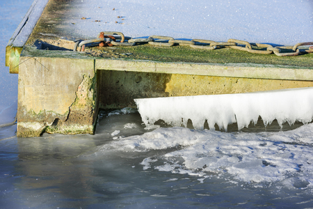 frozen solid: Close up of the end of a floating bridge or pier that has frozen solid into the sea ice.