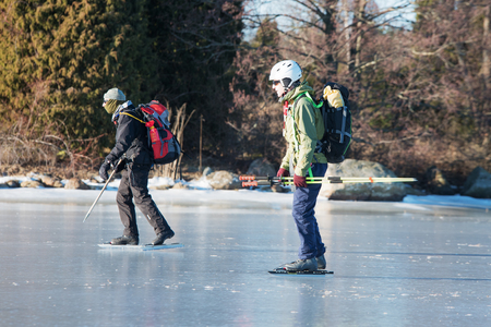Listerby, Sweden - January 17, 2016: Two unknown persons out on a long distance tour skating trip in the archipelago. They have safety gear and one has covered face.  Real people in everyday situation Editorial