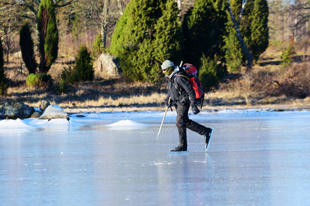 safety gear: Listerby, Sweden - January 17, 2016: Unknown person out on a long distance tour skating trip in the archipelago. Person have safety gear and covered face.  Real people in everyday situation.