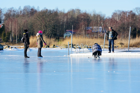 natural ice pastime: Listerby, Sweden - January 17, 2016: Four unknown persons are involved in a discussion at a pier. Ice cover the sea. Three persons are on the ice. Real people in everyday situation.