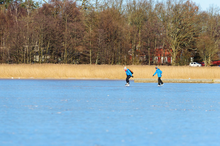 Listerby, Sweden - January 17, 2016: Two unknown persons are out skating in the Blekinge archipelago. Fine ice and reed in background. Real people in everyday situation.