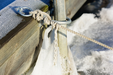 twined: Close up of white rope tied to a pier in winter.