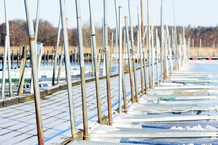 erected: A pier at a marina in winter. The wooden floor is frosty and there are no boats in the marina. Lots of metal poles stand erected along the walkway. Sea is frozen solid. Listerby, Sweden.