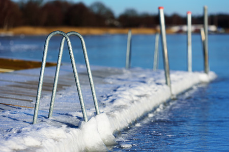 A swimming dock or bathing pier has frozen solid in the sea ice at winter. Seen from the sea with the main land in background. Handles of a bathing ladder go down to the ice.
