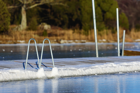 frozen solid: A swimming dock or bathing pier has frozen solid in the sea ice at winter. Seen from the sea with the main land in background. Handles of a bathing ladder go down to the ice.