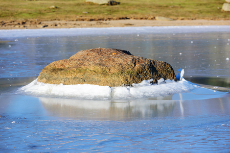 lowers: A granite boulder pushes through the ice surface as the ice level lowers. This forms a fine ice hill around the stone. A natural ice formation with beauty. Natural forces at play. Stock Photo