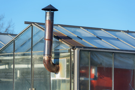 stove pipe: A small metal chimney stick out from a greenhouse with a heater inside.