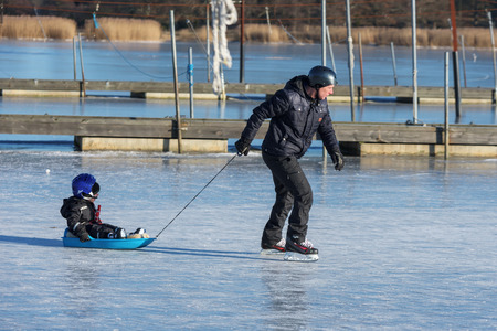 Listerby, Sweden - January 17, 2016: Unknown man pull a small child in a plastic sledge in a frozen marina. Real people in real life having fun together. Editorial