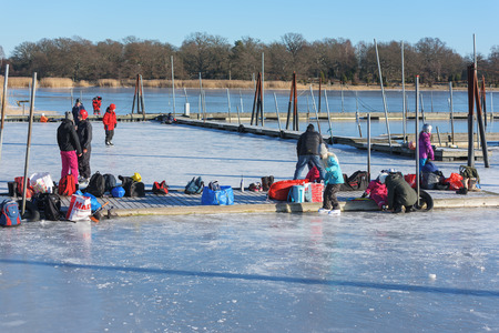 Listerby, Sweden - January 17, 2016: People getting ready to ice skate in the marina. Bags and stuff on the small pier. Real people in real life having fun together.