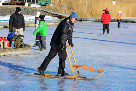 marina life: Listerby, Sweden - January 17, 2016: Unknown adult male on sea ice with a kicksled or spark. Active people havin fun on ice in background. Real people in everyday life in the marina at winter.