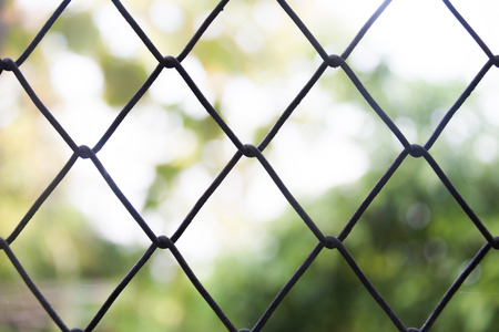 Steel wire mesh fence on a blurred background