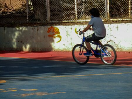 Boy learns to ride a bicycle on the basketball court