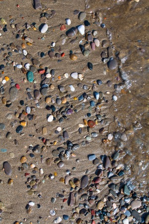 foreshore: wave on the shore with colored stones Stock Photo