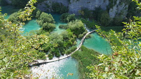 wooden footbridge on a lake seen from the top of a hill Stock Photo