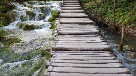 wooden footbridge on a lake with little waterfalls