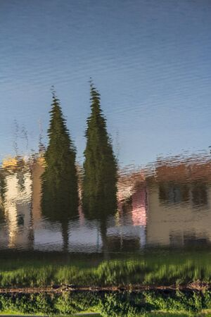 two trees and houses reflected on the water of a river
