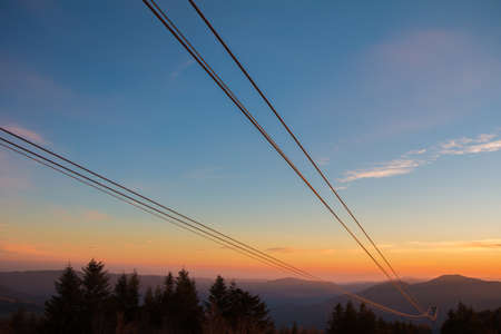 sunset through the cables of a cable car that go downstream