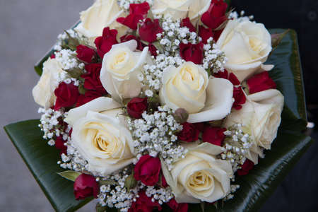 BOUQUET OF RED AND WHITE ROSES OF A BRIDE AT HER WEDDING