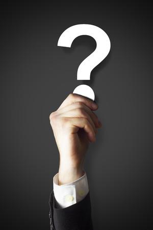 deliberation: businessman holding question mark dark Stock Photo