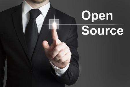 オープン ソースの仮想ボタンに触れるスイートの男 写真素材