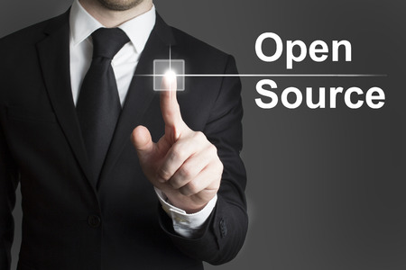 man in suite touching virtual button open source