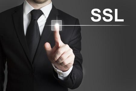 man in suite touching virutal button ssl Standard-Bild