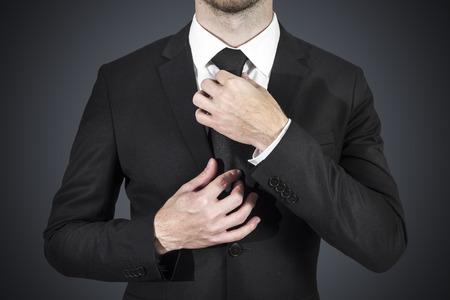 black tie: businessman wearing black suit correcting his tie Stock Photo