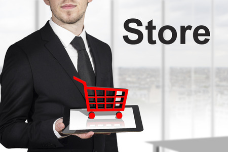 preorder: businessman holding tablet red cart standing in office store