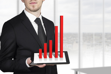 businessman holding tablet red bar graph standing in office