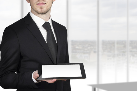 visually: businessman in black suit holding tablet pc with blank touchscreen white Stock Photo