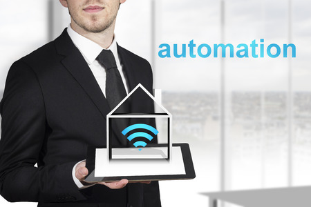 businessman in black suit holding tablet pc with house symbol and automation photo