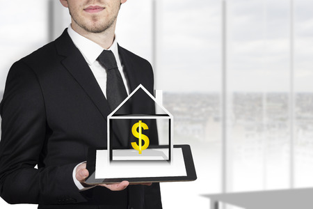 rewarding: businessman with black suit holding tablet pc with 3D house and dollar symbol