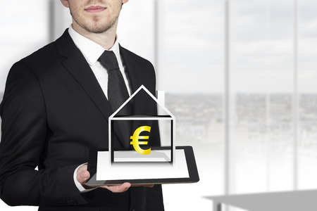businessman in black suit holding tablet pc with 3d house and euro symbol Stock Photo