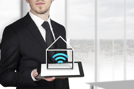 home prices: businessman in black suit holding tablet pc house wireless symbol automation
