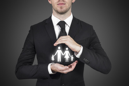 businessman protecting family paper cut with hands Standard-Bild