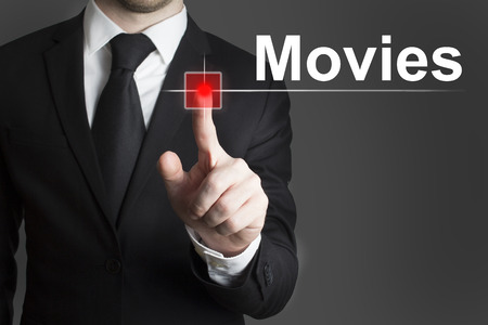 businessman in black suit pushing red touchscreen button movies photo
