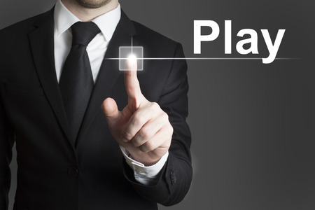 businessman pressing touchscreen virtual play button photo