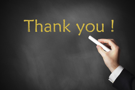 hand writing thank you message on a black chalkboard