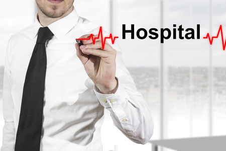 doctor with necktie drawing red heartbeat line in the air hospital