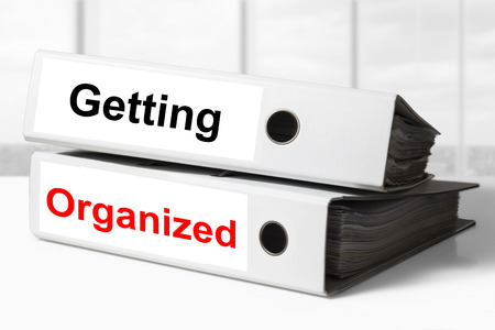 manage clutter: two white office binders getting organized Stock Photo