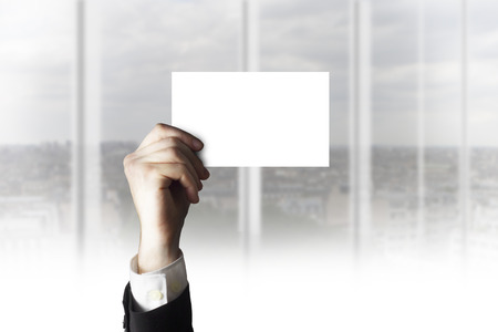 businesscard: businessman hand holding empty white businesscard in the air office room