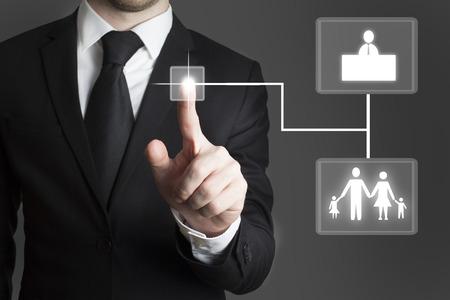 businessman in black suit pressing touchscreen button decision family work Standard-Bild
