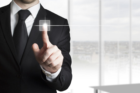 visually: businessman in black suit pressing touchscreen button in light office room