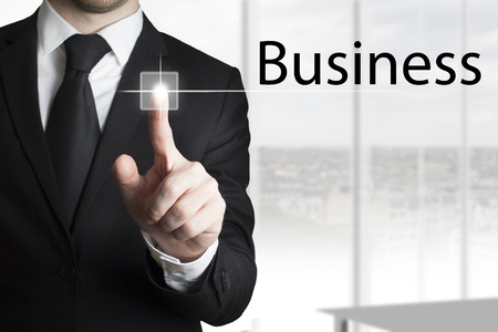 founder: businessman in black suit pressing touchscreen business